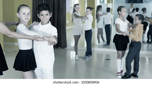 Group of diligent  children dancing tango in dance studio