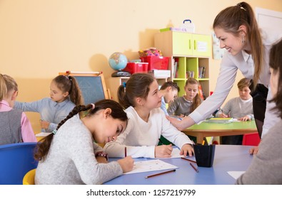 Group of diligent friendly smiling positive  school kids with pens and notebooks studying in classroom with teacher