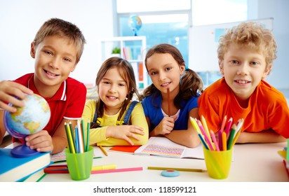 Group of diligent schoolchildren looking at camera in school