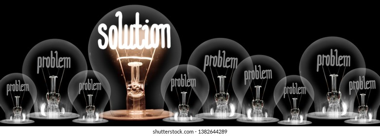 Group of dimmed light bulbs with one of them shining, concept of Problems and Solution, isolated on black background