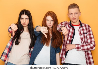 Group of disappointed school friends showing thumbs down while standing together over yellow background