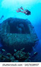 Group of divers explore the wreck, Red Sea, Egypt.