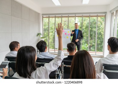 Group of diverse business man and woman attending meeting or seminar in meeting room of an office and one attendant want to ask some question or give an opinion by raising his hand.