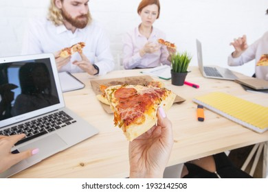 Group of diverse business people eating pizza at break while working together in an office sitting around desk