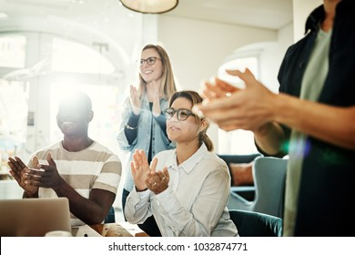 Group of diverse businesspeople clapping during a presentation while working together in a modern office