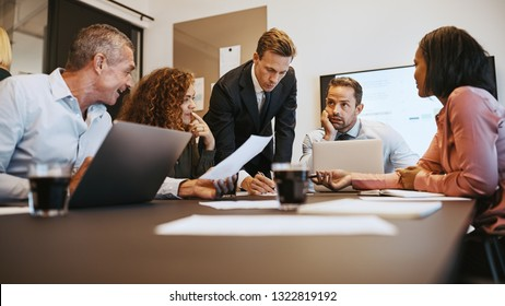 Group of diverse businesspeople discussing paperwork while working together around a table in an office boardroom during a meeting