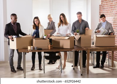 Group Of Diverse Businesspeople Packing Their Belongings In Cardboard Box At Office