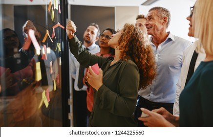 Group of diverse businesspeople strategizing with sticky notes on a glass wall while working together in a modern office