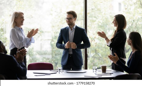 Group of diverse colleagues congratulating applauding and cheering happy businessman with business achievements, career advance, great work results, job promotion standing in modern office board room