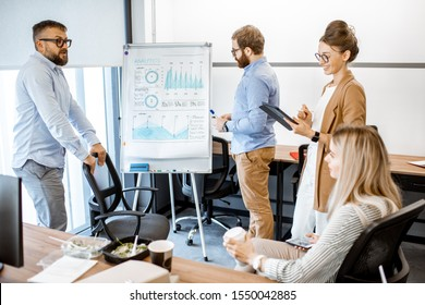 Group of diverse colleagues discussing some working momets with presentation on flipchart during a small conference in the office
