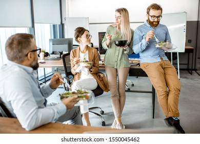 Group of diverse colleagues eating takeaway salad, sitting together and having fun during a lunchtime in the office