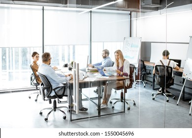 Group of diverse colleagues working on the computers in the modern office or coworking space, wide intreior view