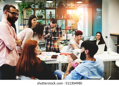 Group of diverse college students sitting together and studying on campus. Friends or business colleagues talking and discussing work ideas in office during informal meeting. Concept of team startup