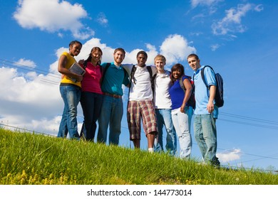 A group of diverse college students/friends outside on a hill with a sky background