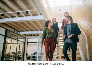 Gruppe unterschiedlicher Mitarbeiter, die die Treppe in einem Büro hinunterlaufen