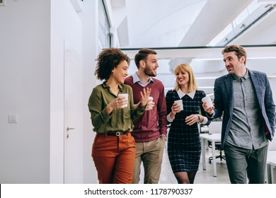 Group of diverse coworkers walking through a corridor in an office, holding paper cups