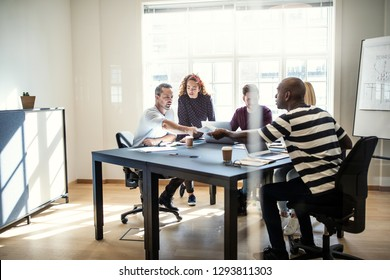Group of diverse designers discussing paperwork together while sitting around a boardroom table inside of an office