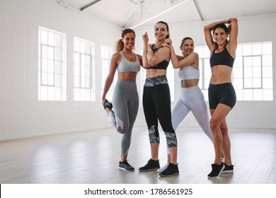 Group of diverse fitness women enjoying workout at a gym studio. Cheerful athletic women doing warm up exercises before fitness training.