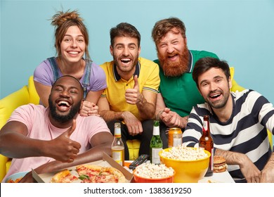 Group of diverse friends cheer as favourite team wins, show thumb up gesture, eat tasty pizza and popcorn, smile broadly, drink beer, isolated over blue background. People, entertainment, fun concept