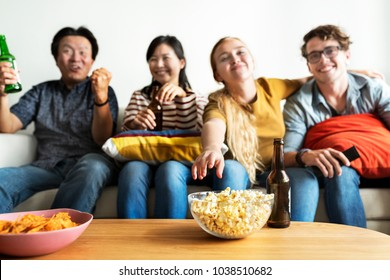 Group of diverse friends having a movie night drinking beer