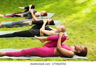 Group of diverse girls stretching their leg during yoga class outside, copy space. Panorama