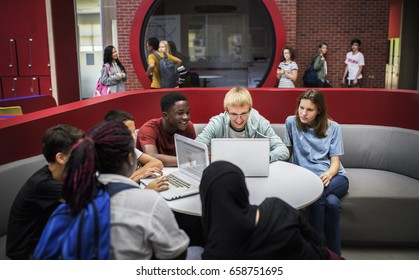 Group of diverse high school students using laptop