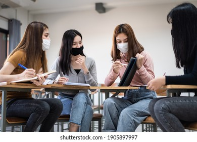 Group of diverse international students wearing protective  masks and talking, discussing project, sitting at desk in the classroom at the university