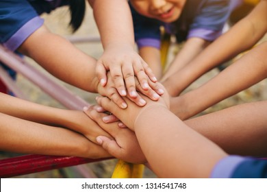 Group of diverse kids hands of together joining for teamwork, community,  togetherness and collaboration concept.