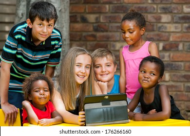 Group of diverse kids playing together on digital tablet outdoors.
