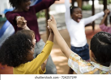 Group of diverse kindergarten students hands up together