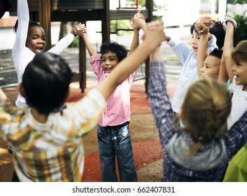 Group of diverse kindergarten students standing holding hands together