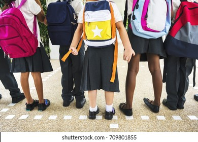 Group of diverse kindergarten students standing together in school