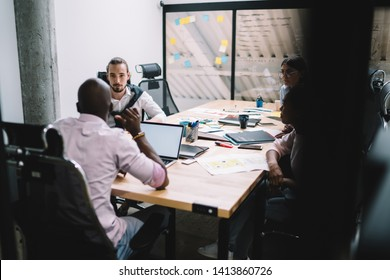 Group of diverse male and female professionals dressed in formal wear discussing business plan for developing project during collaborative process in modern office, concept of entrepreneurship