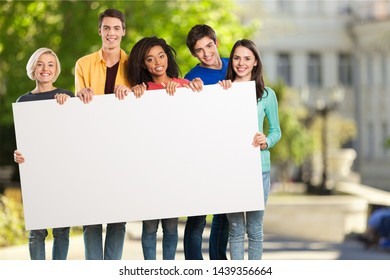 Group of diverse multiethnic happy young people posing with a blank white rectabgular sign with copyspace for your advertisement or text