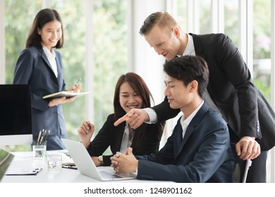 Group of diverse nationality professional look business man and woman meeting or reporting business result or financial report in meeting room and a boss or leader praises or applaud his team member.