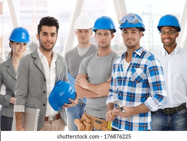 Group of diverse people from building industry: architects, managers, workers posing together for a team portrait.