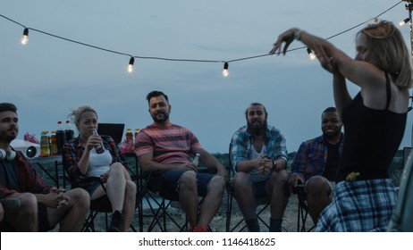 Group of diverse people chilling around bonfire in campsite and playing charades with woman acting and showing pantomime to others
