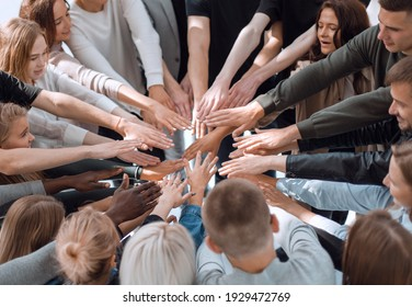 group of diverse people joining their hands in a circle.