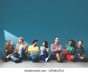 Group of diverse people in a row sitting on the floor