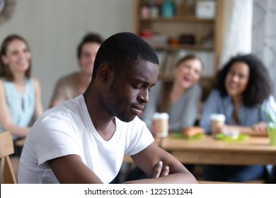Group diverse people sitting in cafe laughing scoffing at black guy. Focus on sitting separately man feels upset and unhappy, schoolmates not take him to their company. Racial discrimination concept