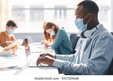 Group of diverse people sitting at the table, working, studying for test, making project or homework together, wearing surgical masks. African american man with headphones using laptop at workplace