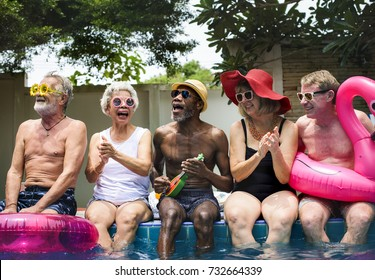 Group of diverse senior adults sitting by the pool enjoying summer together