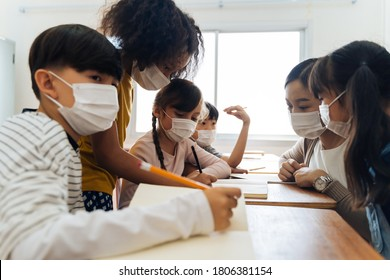 Group of diverse students in school building discussing in group study class. Elementary pupils are wearing a face mask while brainstorming. Covid-19 school reopen concept