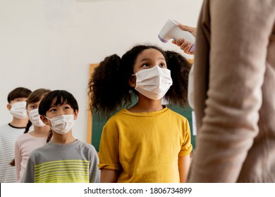 Group diverse students in school building checked and scanned for temperature check. Elementary pupils are wearing a face mask and line up before entering into classroom. Covid19 school reopen concept