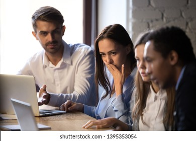 Group diverse surprised colleagues sitting at desk looking at computer screen looks feels shocked baffled puzzled received corporate message. Bad news, critical error, dismissal big problems concept