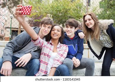 Eine Gruppe von Jugendlichen in der Stadt, die mit Smartphone Fotos mit lustigen Ausdrücken macht, modische Freunde im Freien. Jugendliche vernetzen Technologie, Freizeitlifestyle.