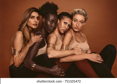 Group of diverse women sitting together against brown background. Multi ethnic females with different skin tones in studio.