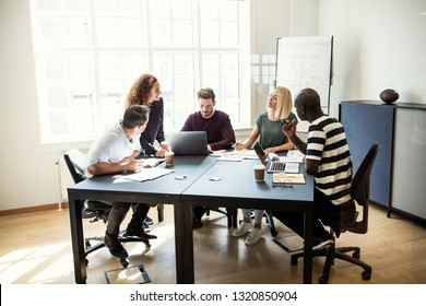 Group of diverse young designers talking together during a meeting in an office boardroom