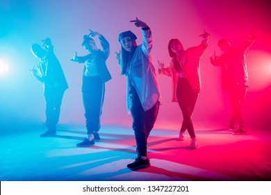Group of diverse young hip-hop dancers in studio with special lighting effects in blue and pink colores