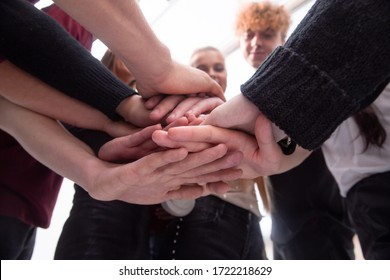 group of diverse young people making a tower out of their hands
